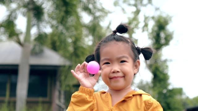 Asian child/girl close up shot smiling holding pink ball/toy green nature background