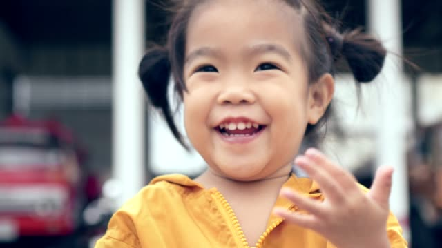 Asian child/girl close up shot smiling holding pink ball/toy