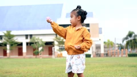 stockvideo's en b-roll-footage met aziatisch kind/meisje houden toon roze bal/speelgoed op groene gras natuurpark - babymeisjes