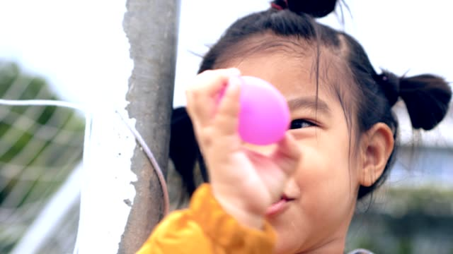 Asian child/girl in soccer goal looking and smiling enjoyment holding pink ball