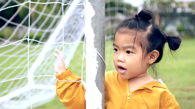 Asian child/girl in soccer goal looking and smiling enjoyment