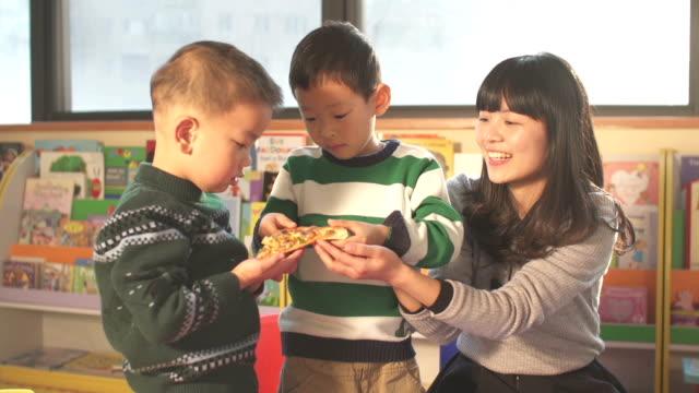 stockvideo's en b-roll-footage met asian children and preschool teacher eating pizza in classroom - peuterschool gebouw