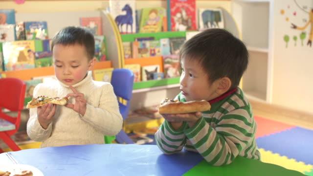 Asian children and preschool teacher eating pizza in classroom