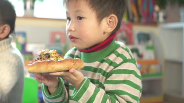 asian children and preschool teacher eating pizza in classroom - nursery school building stock videos and b-roll footage