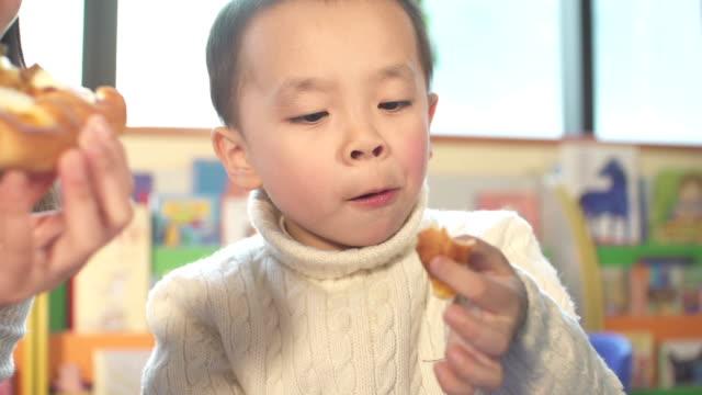 asiatische kinder und kinder, lehrer im klassenzimmer essen pizza - schulessen stock-videos und b-roll-filmmaterial