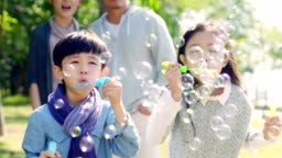 asian children blowing bubbles outdoors