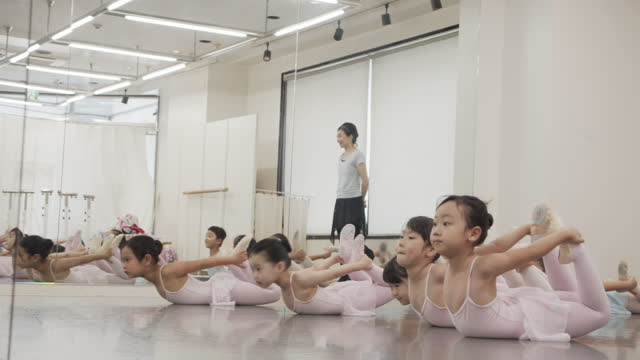 asian children in leotards and asian female instructors are taking ballet lessons in studio - 神奈川県点の映像素材/bロール