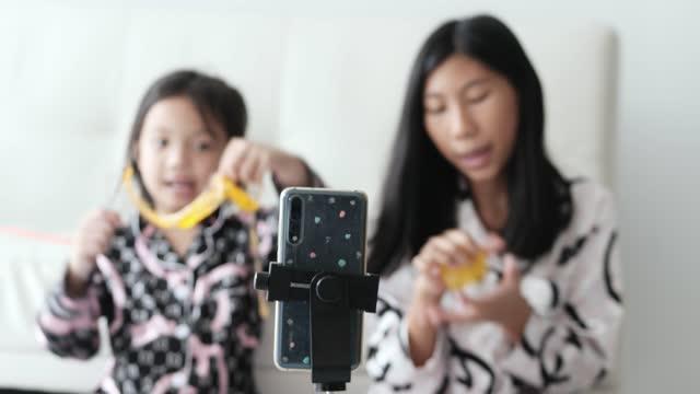 アジアの子供ブログやyoutuberは、自宅で床にクリスタルスライムをレビュー, モダンなライフスタイルのコンセプト. - バイラルビデオ点の映像素材/bロール