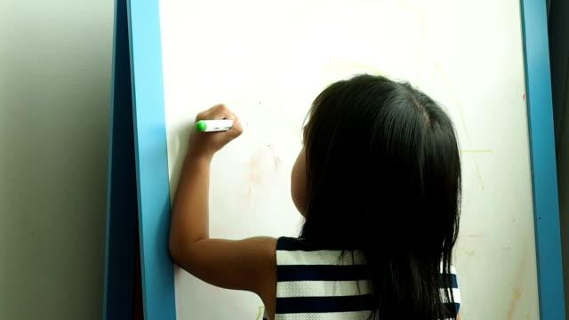 vídeos y material grabado en eventos de stock de dibujo asiático para niños en pizarra con zurdo - a la izquierda de