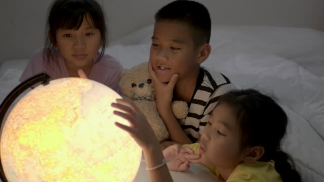 asian children's grop learning about geography at bedroom. - mappamondo video stock e b–roll