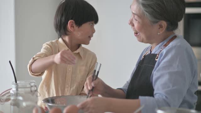 asian chinese 6 years old boy helping his grandmother preparing food with flour baking at kitchen counter together - 65 69 years stock videos & royalty-free footage