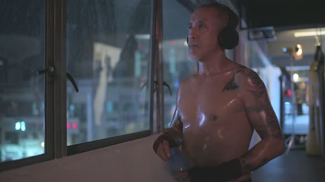 asian chinese active senior man boxer eyes closed listening to music with headphone beside window at gym at night - only mature men stock videos & royalty-free footage