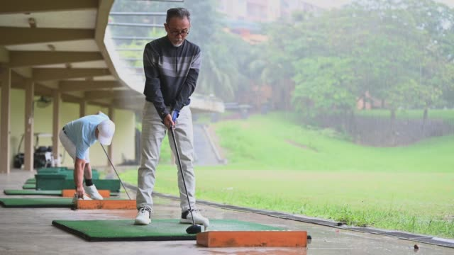 asian chinese active senior man golfer teeing off and swing his diver golf club at golf driving range - senior golf swing stock videos & royalty-free footage
