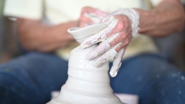 asiatico cinese attivo senior man potter che lavora nel suo laboratorio con ruota di ceramica rotante - craft video stock e b–roll