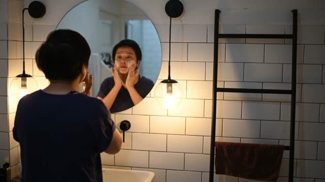 asiatische chinesische anwendung maske auf ihre gesichtshaut in toilette blick auf spiegel - körperpflege stock-videos und b-roll-filmmaterial