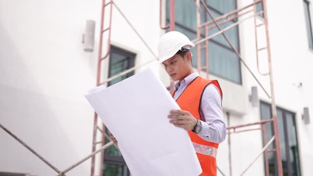 建設現場の進捗状況を際立て立証する青写真を使用したアジアの中国人建築家 - 土木技師点の映像素材/bロール