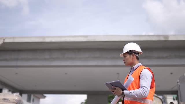 建設現場での進捗状況を刺激するデジタルタブレットを使用したアジアの中国の建築家。 - 土木技師点の映像素材/bロール