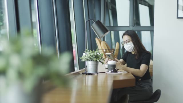 vídeos y material grabado en eventos de stock de chino asiático en la cafetería disfrutando de la comida y relajarse fin de semana con nueva máscara de cara normal de uso - cultura de café
