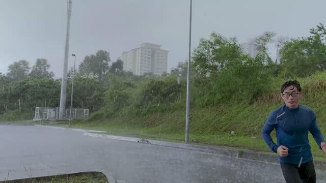 vidéos et rushes de l'homme chinois asiatique d'athlétisme dans la tenue de sport fait le jogging dans la rue sur une pluie - adversité