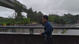 Asian Chinese Athletic man in sports outfit is jogging in the street on a rain