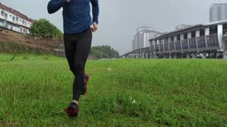 Asian Chinese Athletic man in sports outfit is jogging through puddles in the grass on a rain.