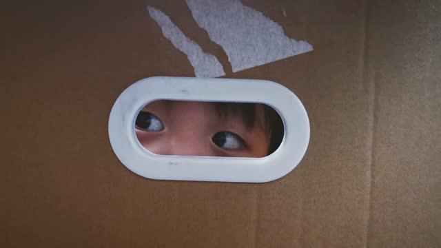 asian chinese baby boy peeking through ellipse hole on cardboard box hiding in cardboard box, looking out with window frame shadow - babies only stock videos & royalty-free footage