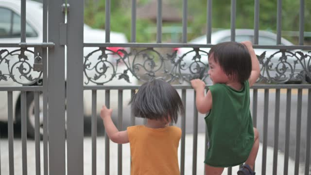 stockvideo's en b-roll-footage met asian chinese baby boy playing climbing gate in front of house during summer weekend - chinese etniciteit