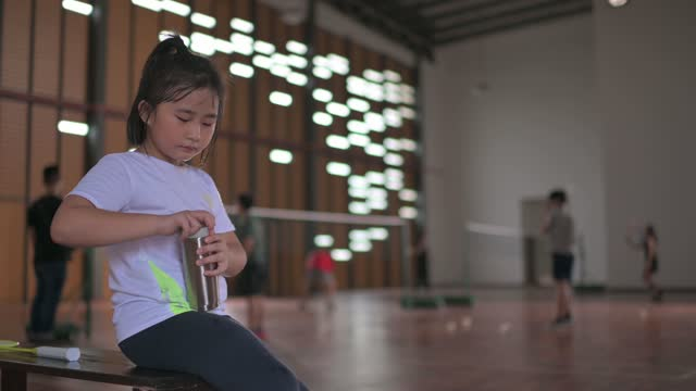 asian chinese badminton young girl players taking a break at the edge of badminton court drinking water - water bottle stock videos & royalty-free footage