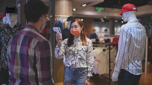 アジアの中国の美しい女性のメンズウェア店のオーナーは、顔マスクが標準的な手順として赤外線温度計を指し示す体温をチェックし、新しい通常としてカフェに入る前にプロセスをチェッ� - 温度計点の映像素材/bロール