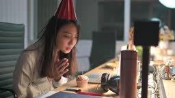asian chinese beautiful woman alone working late in office celebrating her birthday video conference with her colleague at other branch