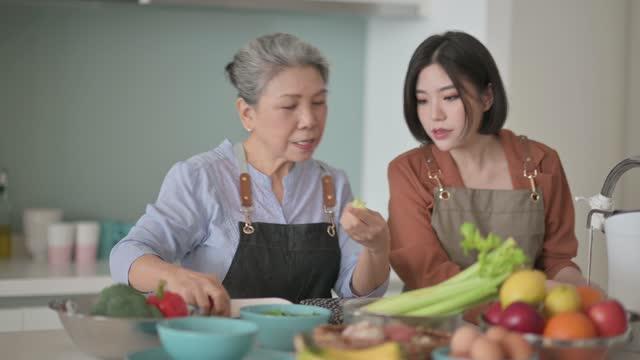 vidéos et rushes de femme chinoise asiatique belle et sa mère obtenant les repas de cuisson prêts pour la famille au compteur de cuisine - apprentissage