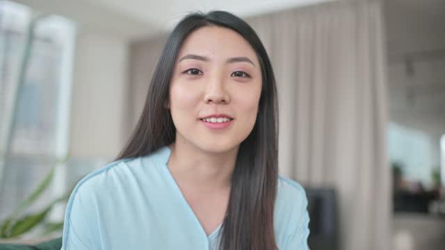 asiatische chinesische schöne frau blickend auf kamera videoanruf lächelnd innen - nur junge frauen stock-videos und b-roll-filmmaterial