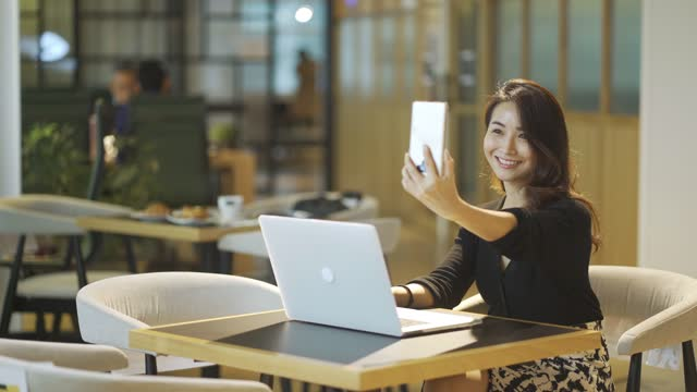 asian chinese beautiful woman sitting in a cafe with social distancing sign and arrangement reading replying phone message with her smart phone while working with her laptop - phone message stock videos & royalty-free footage