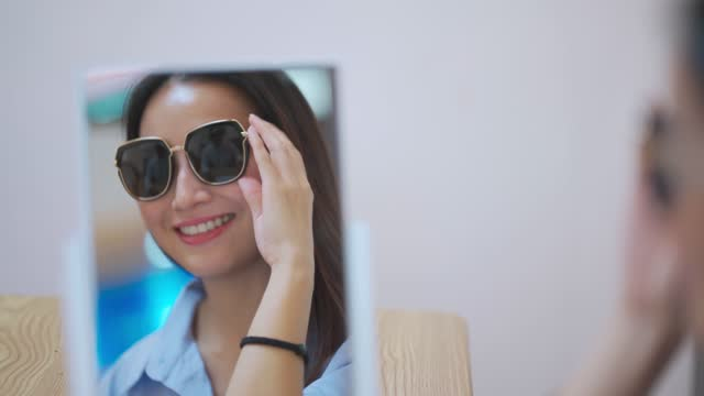 asian chinese beautiful woman trying on sunglasses in front of mirror at optician store - sunglasses stock videos & royalty-free footage