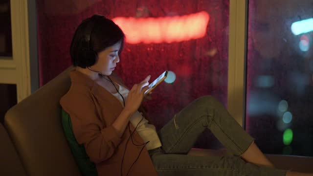 asiatische chinesische schöne frau mit telefon im wohnzimmer auf sofa in der nähe fenster mit stadtlicht in der nacht - abspann stock-videos und b-roll-filmmaterial