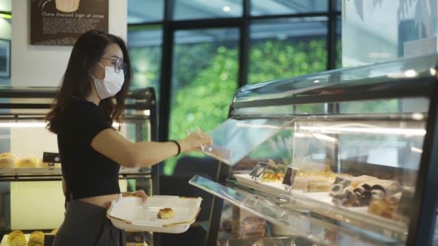 asiatische chinesische schöne frau mit gesichtsmaske auswahl und kauf brotgebäck in einem bäckerei-shop setzen auf tablett - kuchen und süßwaren stock-videos und b-roll-filmmaterial