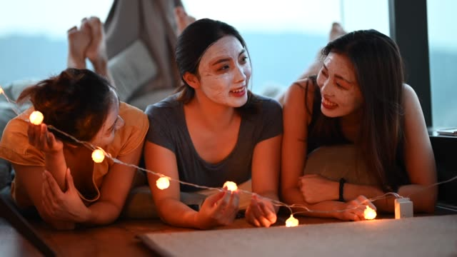 vídeos de stock, filmes e b-roll de 3 mulheres asiáticas chinesas bonitas aplicando máscara de argila no quarto se divertindo em tempo de união - health farm