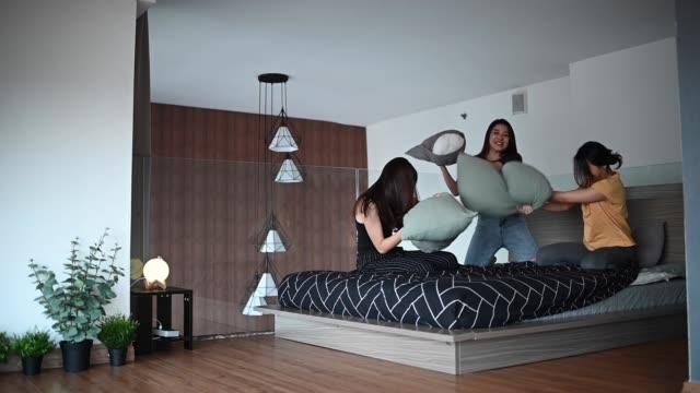 vídeos de stock e filmes b-roll de 3 asian chinese beautiful women spending weekend together at home apartment bonding pillow fight on bed - ditado