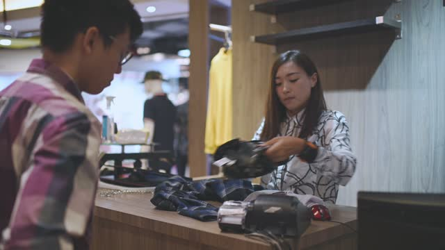 asian chinese boutique shop owner receiving credit card from her customer at cashier check out in menswear clothing store - 20 29 years stock videos & royalty-free footage