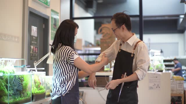asian chinese business owner wife help roll up his sleeves ready for work. - husband stock videos & royalty-free footage