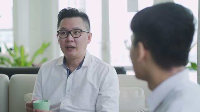 asian chinese business person having discussion at office business lounge sofa having casual discussion - males stock videos & royalty-free footage