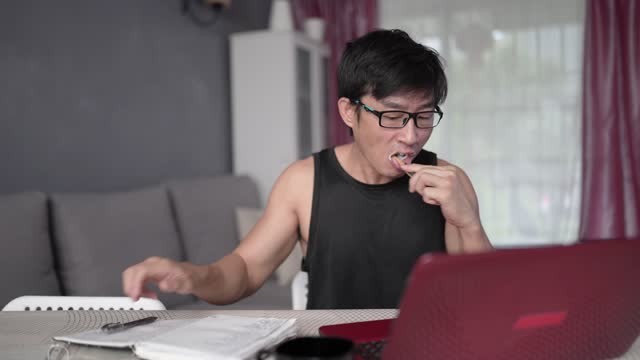 asian chinese businessman exhausted brushing his teeth while using laptop working at home. - one mid adult man only stock videos & royalty-free footage