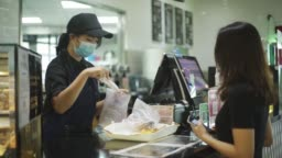 asian chinese cafe cashier servicing her customer scanning for pricing and packing