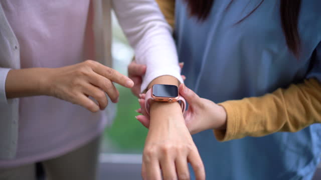 asian chinese caregiver wearing a smart watch on a patient's wrist - trust stock videos & royalty-free footage