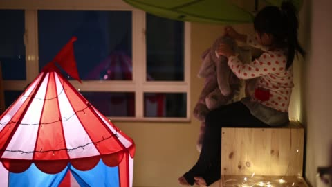 asian chinese child playing in the playroom in the tent hugging a stuffed toy sitting on a cabinet - fortress stock videos & royalty-free footage