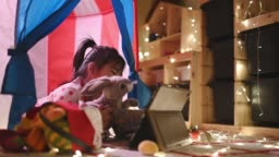 Asian chinese child playing in the playroom in the tent using digital tablet lying down