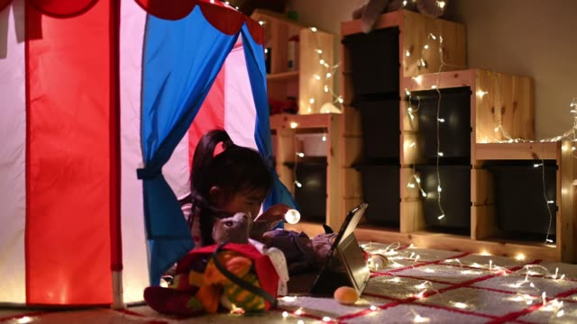 asian chinese child playing in the playroom in the tent using digital tablet lying down - excitement stock videos & royalty-free footage