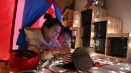 Asian chinese child playing in the playroom in the tent using digital tablet lying down with her mother
