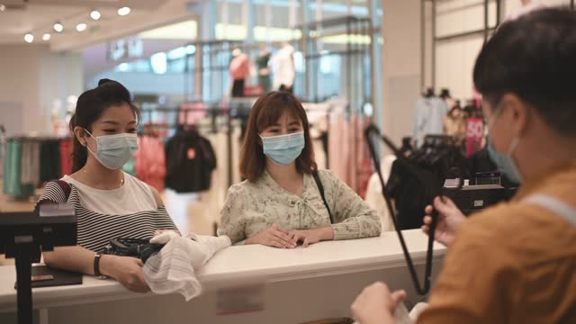 asian chinese clothing store cashier receive credit card from her customers at counter with face mask - clothes shop stock videos & royalty-free footage