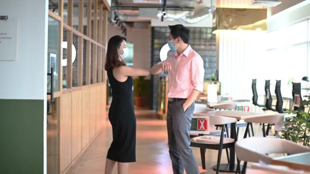 2 asian chinese colleague greeting on each other with new handshake style in office with protective mask on - social grace stock videos & royalty-free footage